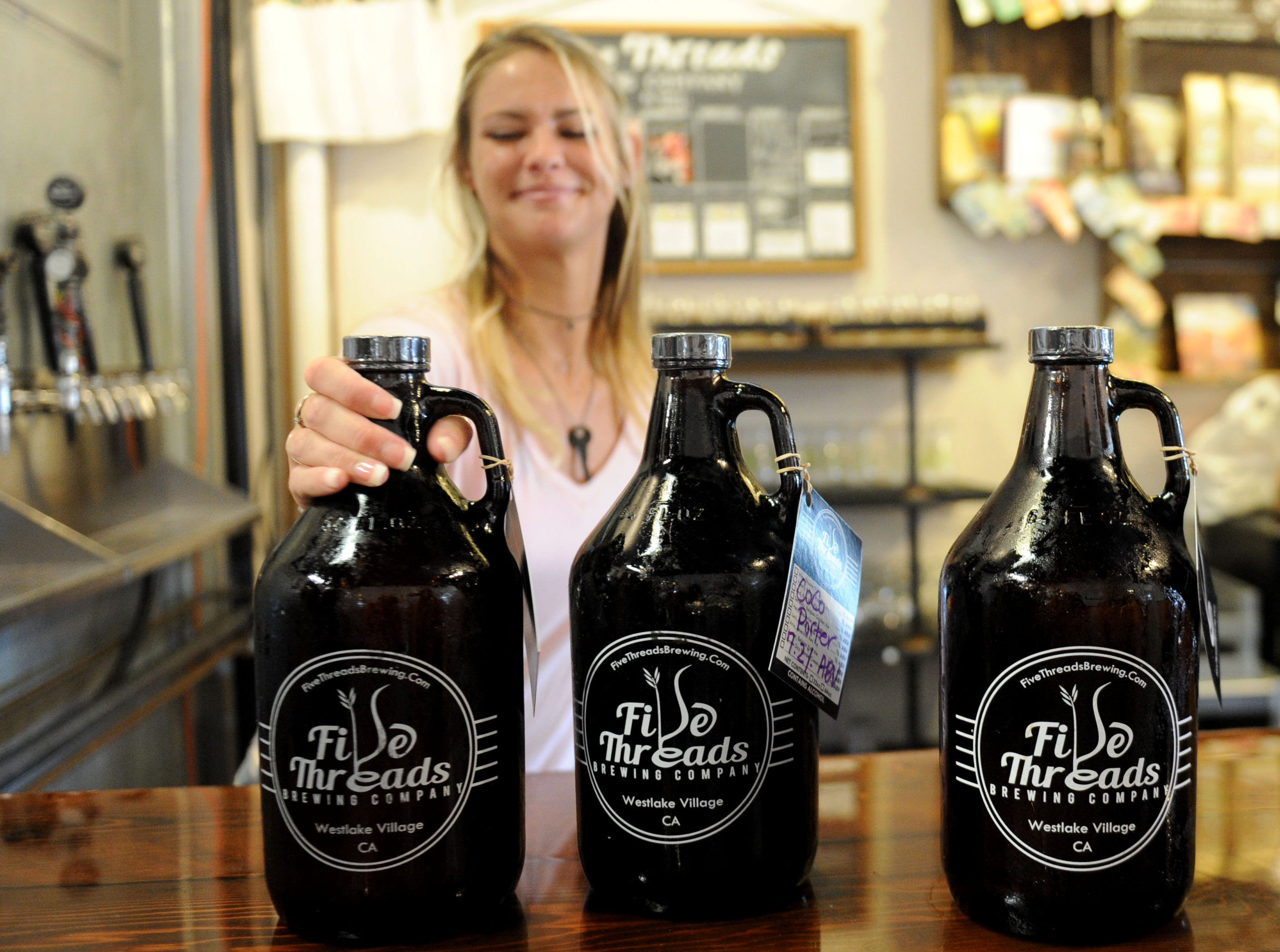 At Five Threads Brewing Company in Westlake Village Brynn Gompf, an executive assistant, finishes filling a 64-ounce growler with beer.