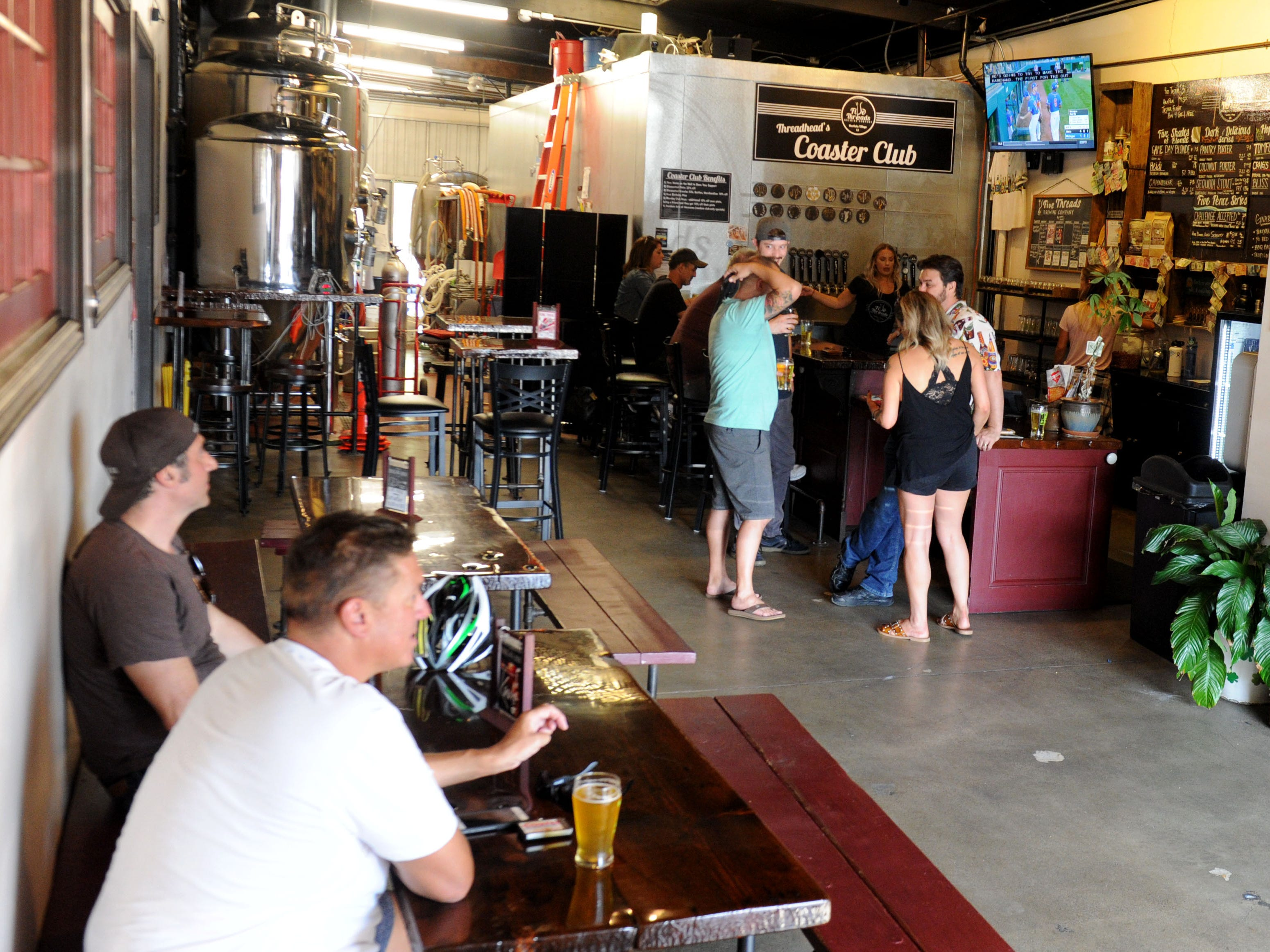 A group of customers enjoy an afternoon beer at Five Threads Brewing Company in Westlake Village.