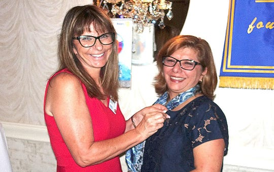 Vineland Rotary Member Sandy Forosisky (left) puts a Rotary pin on returning Rotarian Maryam Nassiri at the Ramada of Vineland during a recent Rotary Club of Vineland membership luncheon.