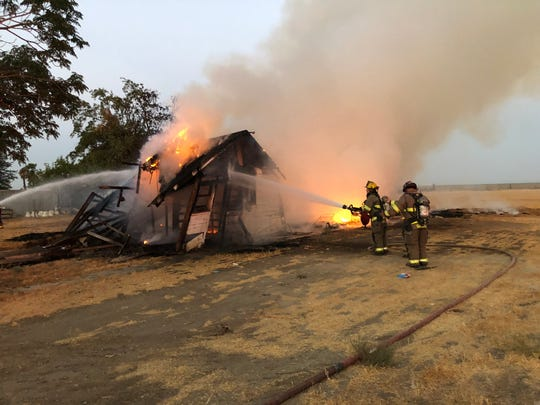 Tulare firefighters work to extinguish flames near O Street and Paige Avenue early Monday morning.