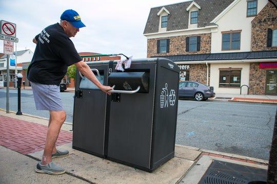 Former Newark Mayor Vance A. Funk III throws away trash he found on Main Street.