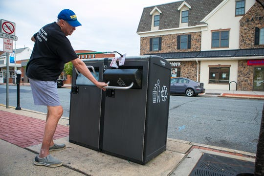 Former Newark Mayor Vance A. Funk III throws away trash he found on Main Street.