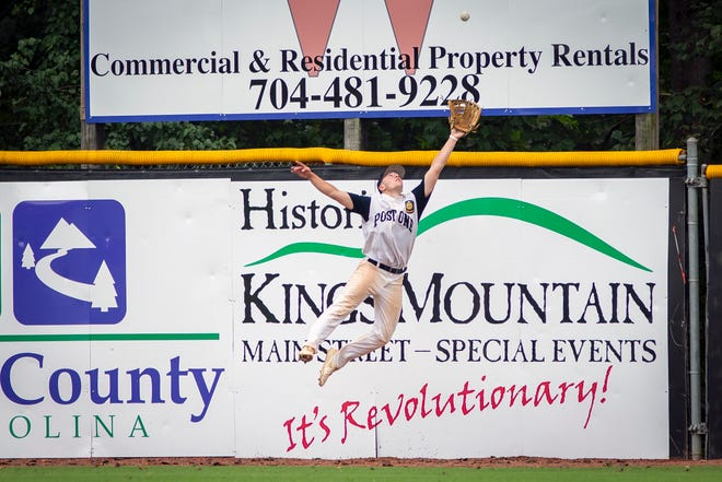 Matt Poma of Post One leaps against the right-field wall to make a clutch sixth-inning catch.