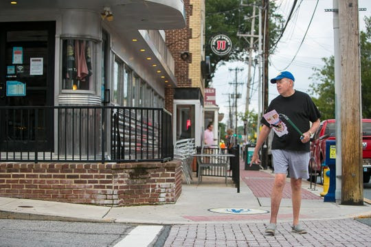 Former Newark Mayor Vance A. Funk III  crosses the street in front of Cheeburger Cheeburger with trash he found.
