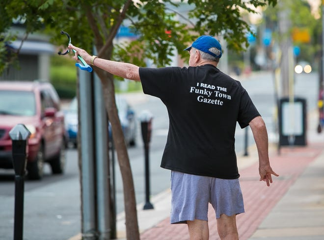 Former Newark Mayor Vance A. Funk III waves to passers-by along Main Street as he picks up trash on Monday, August 20.