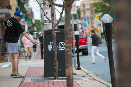 Former Newark Mayor Vance A. Funk III cleans Main Street.