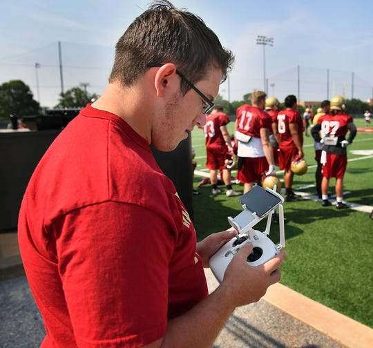 Freshman Josiah Robbins works as a student manager with the Mustangs football program and pilots a quadcopter drone, shooting aerial video during practice.
