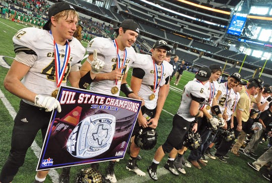Several Crowell players hold a championship banner after their 78-52 win over May at the UIL football Six-Man Division I state championship game at AT&T Stadium in Arlington Saturday afternoon.
