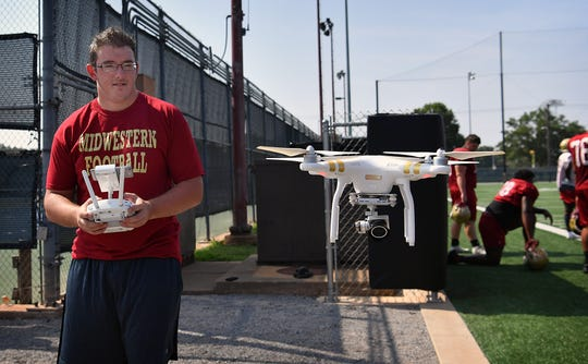 Josiah Robbins, a freshman at Midwestern State University, prepares to land his quadcopter drone Monday after recording video at MSU Mustangs football practice.