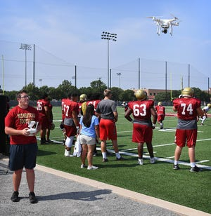 Midwestern State University freshman Josiah Robbins brings his quadcopter drone in for a fresh battery Monday morning during MSU football practice. Robbings provides aerial video footage of formations and plays for coaches and players to analyze.