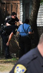 Wichita Falls police try to coax a wounded pit bull dog after they shoot and wound it and kill another while serving a warrant in the 1400 block of 25th Street, Monday afternoon.