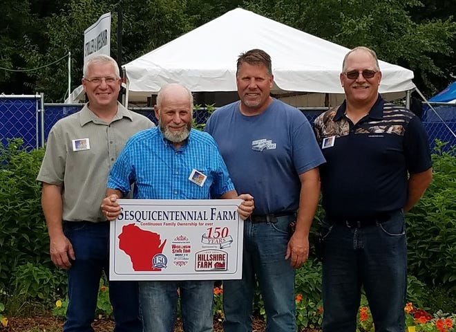 Dean Melcher (with sign) was joined by his three sons Gary, Greg and Grant, in a celebration of their family's 150 years of farming in Jefferson County. They were honored with other farm families at the Wisconsin State Fair.