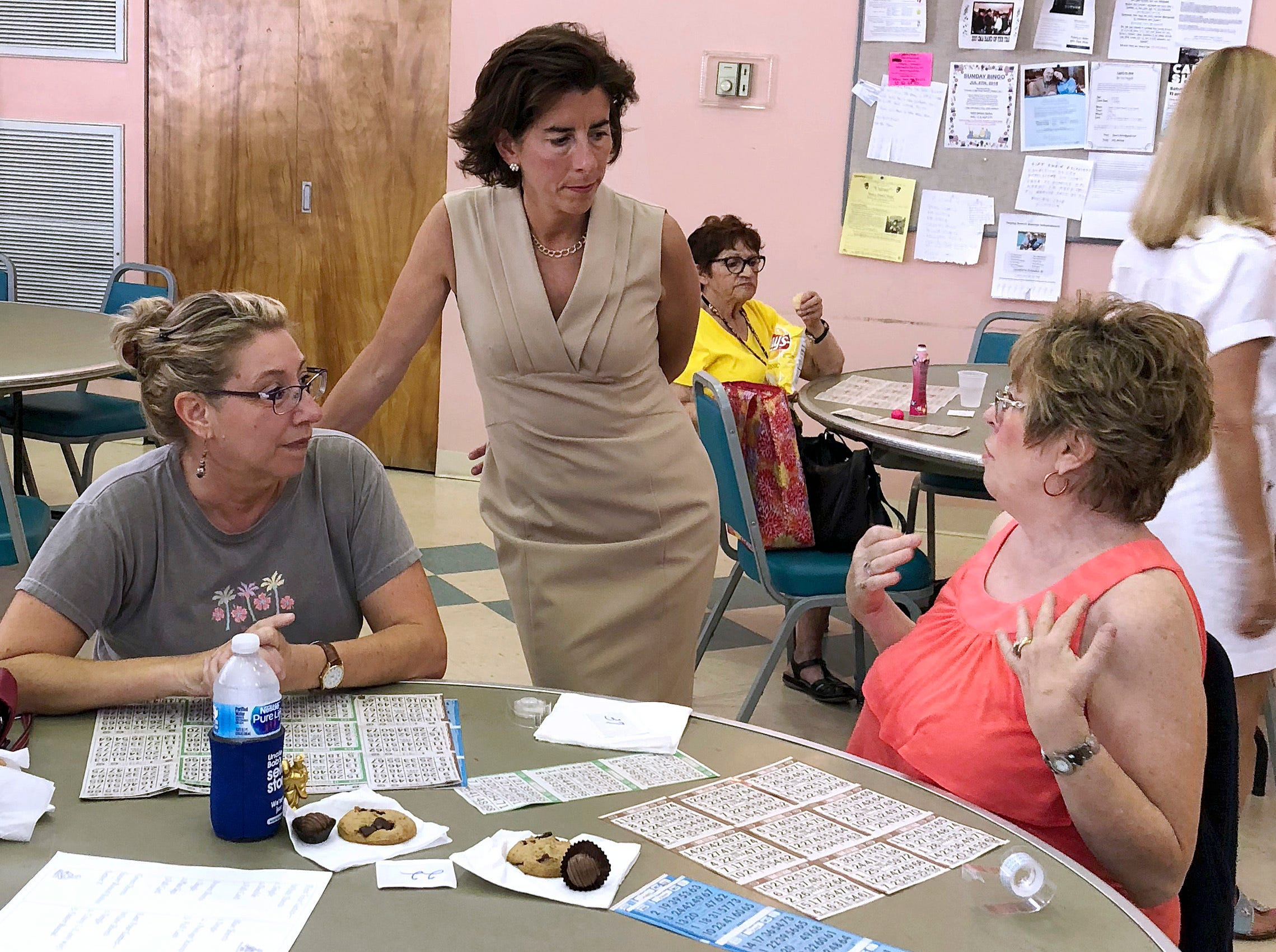 FILE- In this Aug. 2, 2018, file photo, Rhode Island Gov. Gina Raimondo, center, speaks with Lisa McGovern, left, and Betty Toye at the Pilgrim Senior Center in Warwick, R.I. Raimondo and U.S. Rep. Gwen Graham of Florida are among nine women running for governor who will face primary voters in coming weeks. No more than nine women have ever led states at the same time.