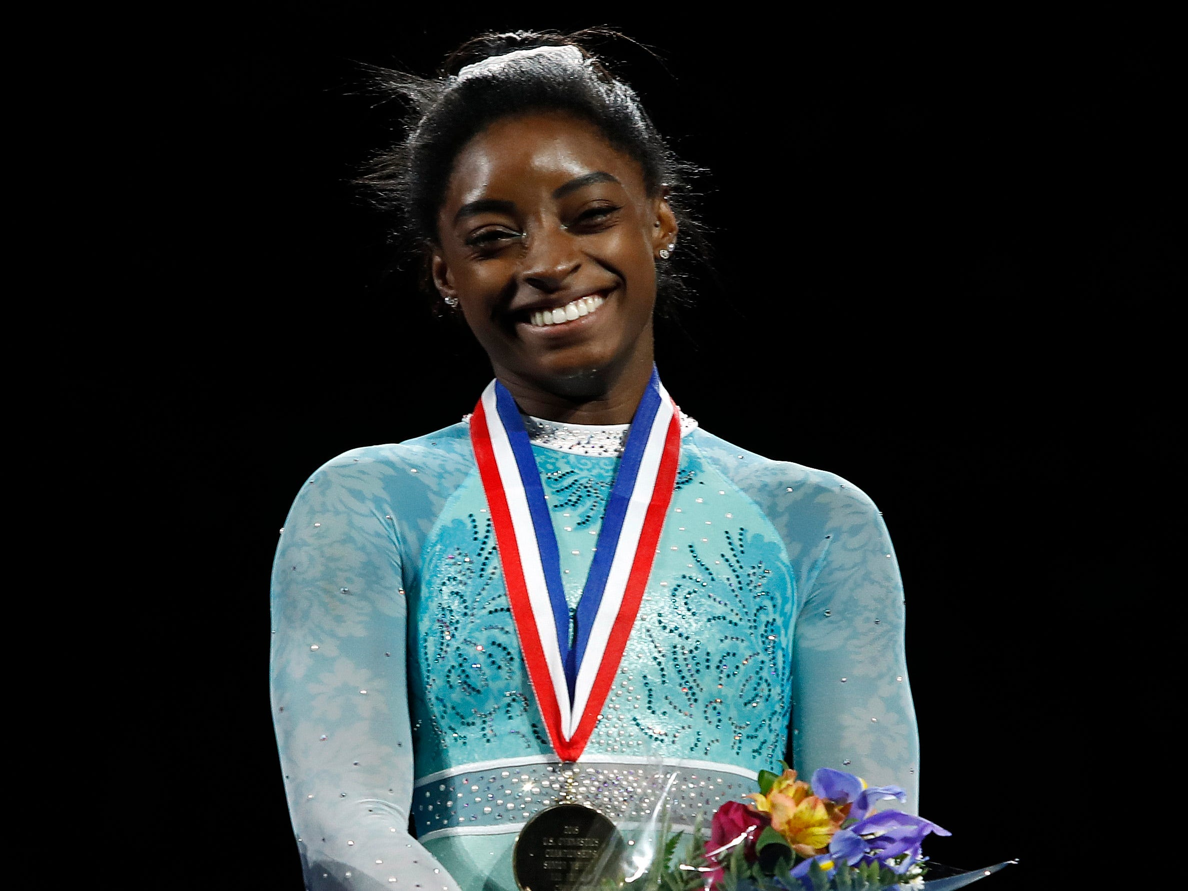 Simone Biles smiles after winning the women's all-around during the U.S. Gymnastics Championships.