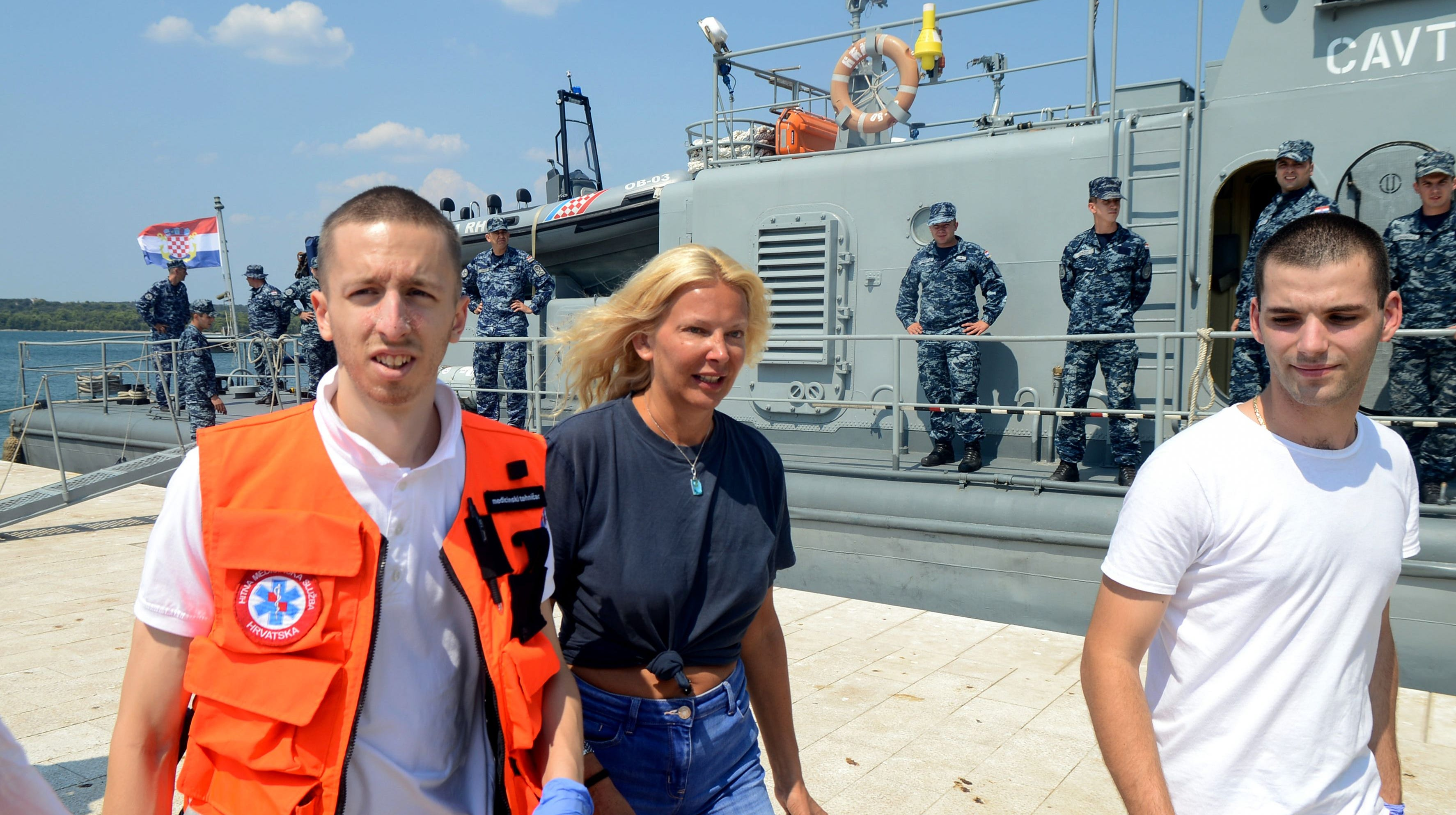 British tourist Kay Longstaff, center, exits Croatias coast guard ship in Pula, on August 19, which saved her after falling off a cruise ship near Croatian coast.