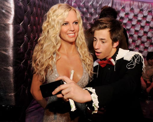 Actor Jimmy Bennett poses with a wax statue of Britney Spears at a Hollywood party of Madame Tussaud on January 23, 2013 in Los Angeles.