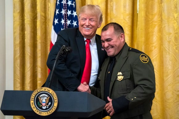 President Donald Trump shakes hands with Border Patrol Agent Adrian Anzaldua during an event to honor federal immigration agents in the East Room of the White House in Washington, on Aug. 20 2018.