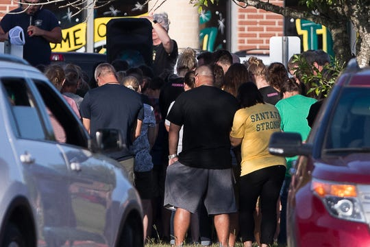 People attend a vigil outside Santa Fe High School in Santa Fe, Texas, on Aug. 19 2018. The vigil was held the day before the first day of school. On May 18, 2018, eight students and two teachers were killed in a mass shooting.