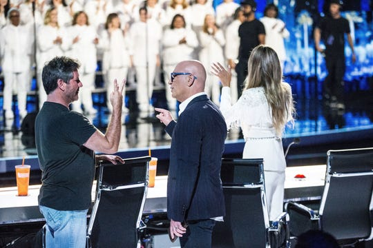 'AGT' judges Simon Cowell, left, and Howie Mandel talk as fellow judge Heidi Klum looks toward the Angel City Chorale during the Aug. 14 episode.