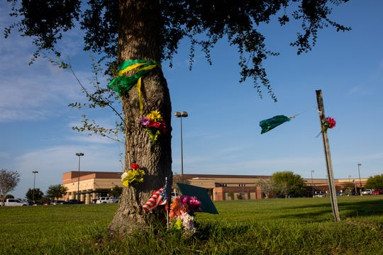 Ribbons, flags and flowers sit around a tree outside Santa Fe High School in Santa Fe, Texas, on Aug. 19, 2018. The vigil was held the day before the first day of school. On May 18, 2018, eight students and two teachers were killed in a mass shooting.