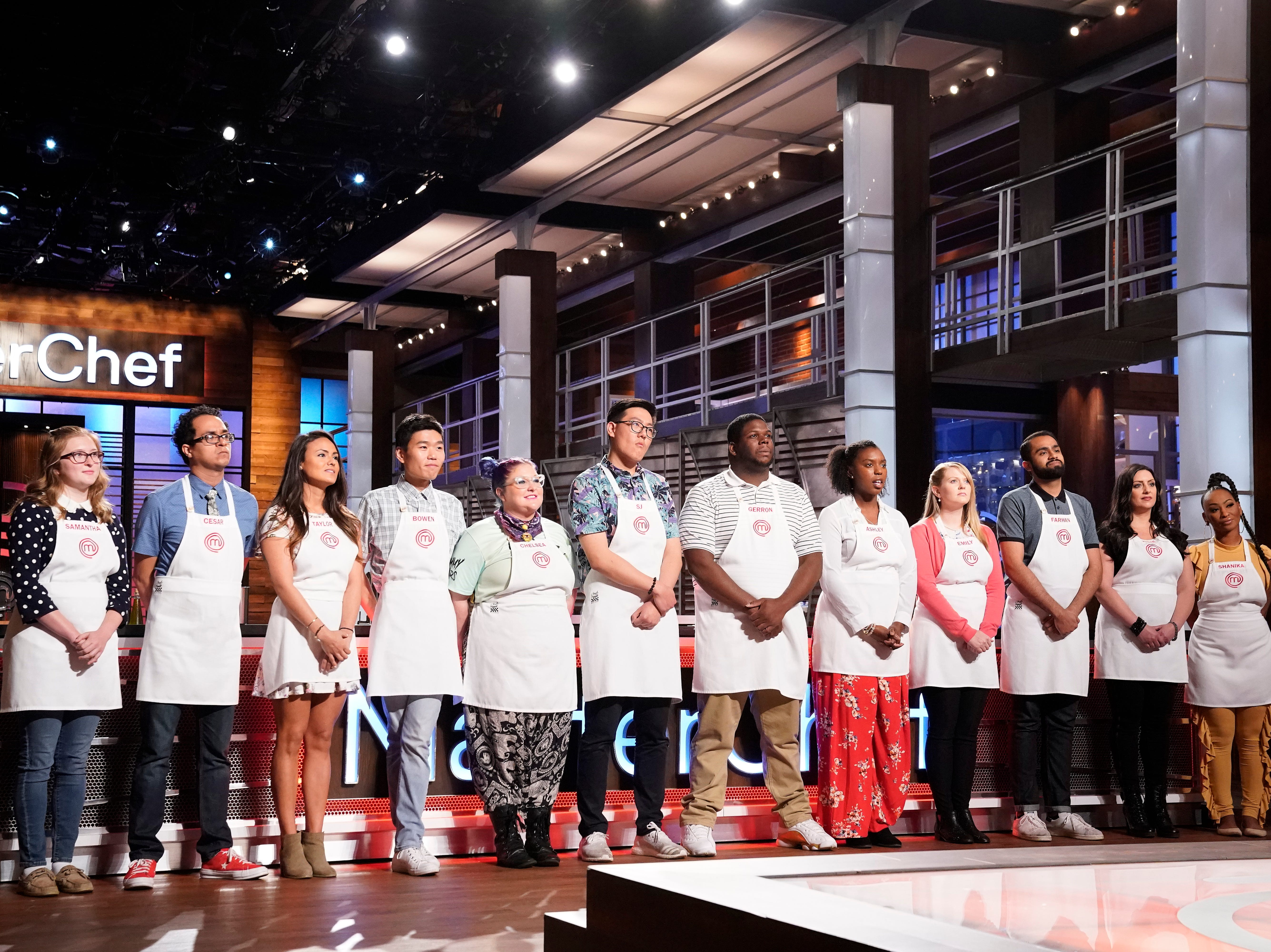 "Emily Hallock (fourth from right) and 11 remaining contestants are about to get a lesson from Gordon Ramsay on how to filet and portion a halibut for a skills challenge. During the ninth season of ""MasterChef,"" Hallock consistently excelled at skills challenges."