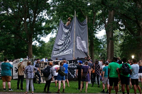Banners are used to cover the statue known as Silent Sam as people gather during a rally to remove the confederate statue from campus at the University of North Carolina in Chapel Hill on Monday, Aug. 20, 2018.