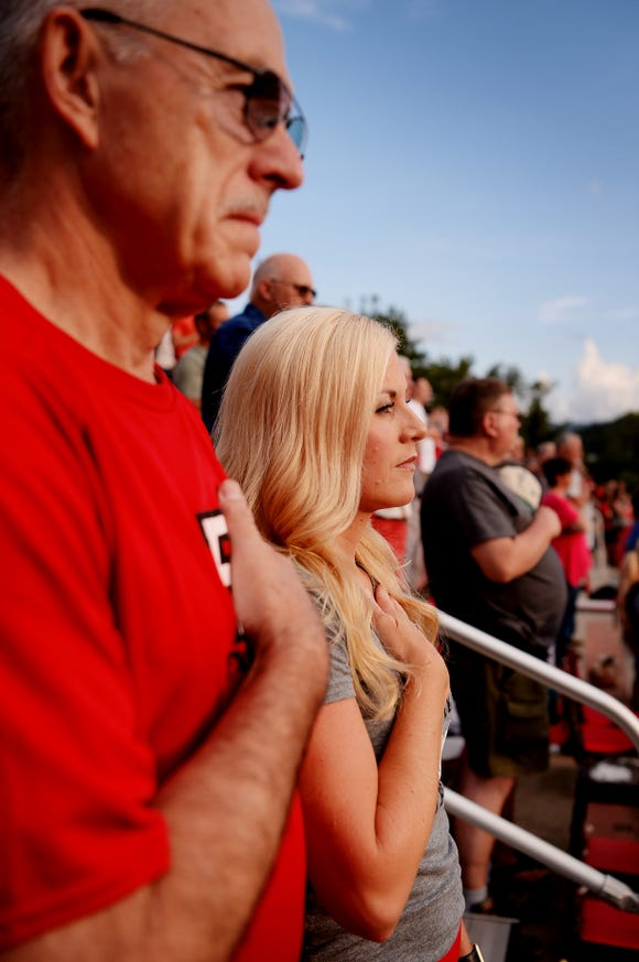 Lori Chappell and her father-in-law, Troyce, listen to the National Anthem before Pisgah takes on Murphy August 17, 2018 in Canton.