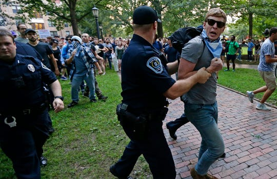 Police remove a protester during a rally to remove the confederate statue known as Silent Sam from campus at the University of North Carolina in Chapel Hill on Monday, Aug. 20, 2018.