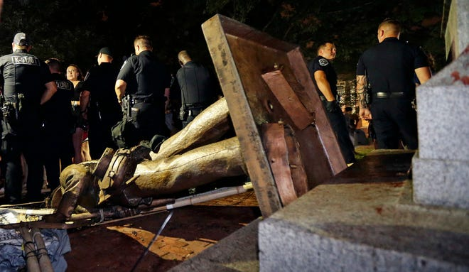 Police stand guard after the confederate statue known as Silent Sam was toppled by protesters on campus at the University of North Carolina in Chapel Hill on Monday, Aug. 20, 2018.