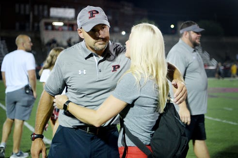 Pisgah head football coach Brett Chappell receives a hug from his wife, Lori, after defeating Murphy 15-8 August 17, 2018 in Canton.