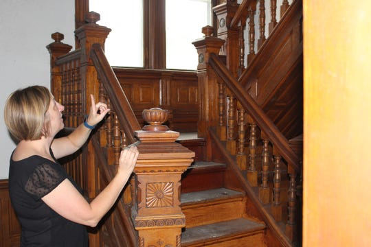 Calhoun County Land Bank Authority Executive Director Krista Trout-Edwards points out some of the features inside the 1870s-built home at 26 Fremont Street.