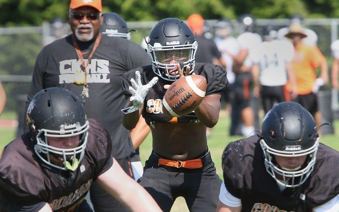 Central Kitsap quarterback Elijah McGee takes a snap during a recent practice.