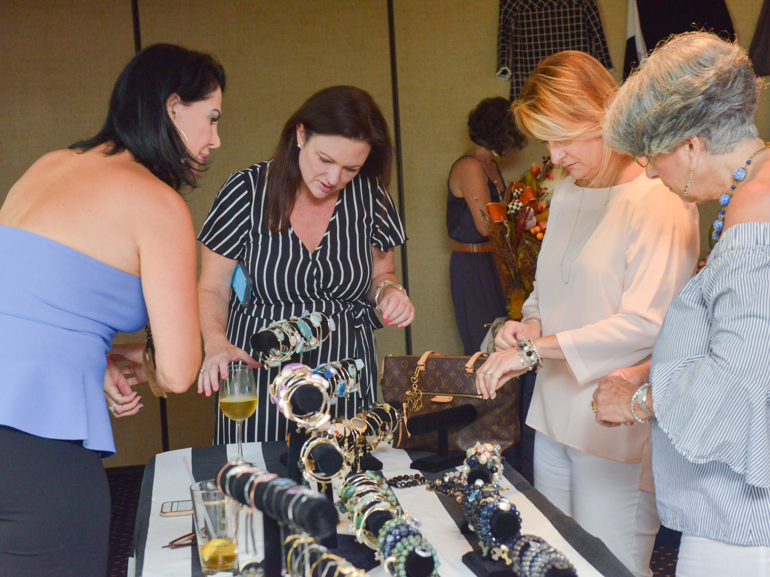 Friends browse jewelry made by Sandra Dee Russell at Friends of Sally's House luncheon at the Eau Gallie Yacht Club.