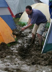 Steve Parker of Windham, N.Y. digs a trench in the mud surrounding his tent as he prepares for his first night camping out at the Phish Festival in Coventry, Vt., Friday, Aug. 13, 2004.