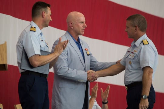 Zachary Pickett receives the Coast Guard Civilian from Rear Admiral Paul F. Thomas (right) and Captain Edward Gaynor during the Hurricane Harvey awards ceremony on Tuesday, August 21, 2018 at Valent Hall.
