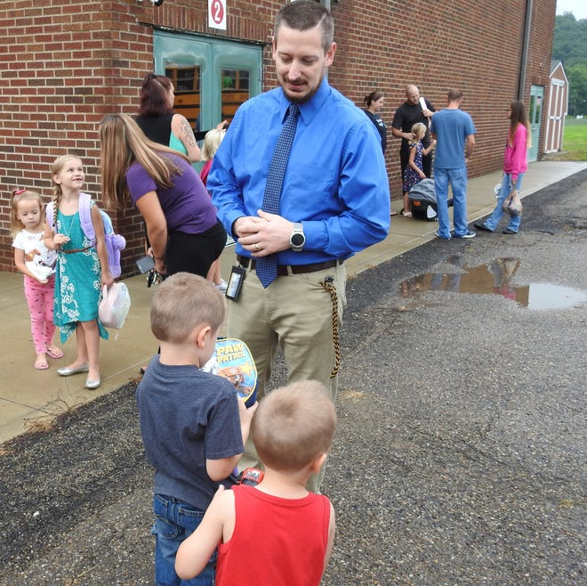 Principal Jarred Renner talks with students on the first day of school Tuesday at Conesville Elementary School. It's Renner's first year at the school, transferring from Union Elementary.