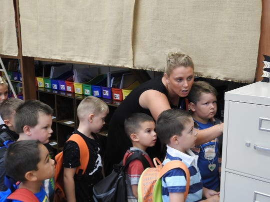 Kindergarten teacher Kimberly Hill show students how to mark what they want to eat for lunch or if they packed their lunch on a magnet board for the first day of school Tuesday at Conesville Elementary.