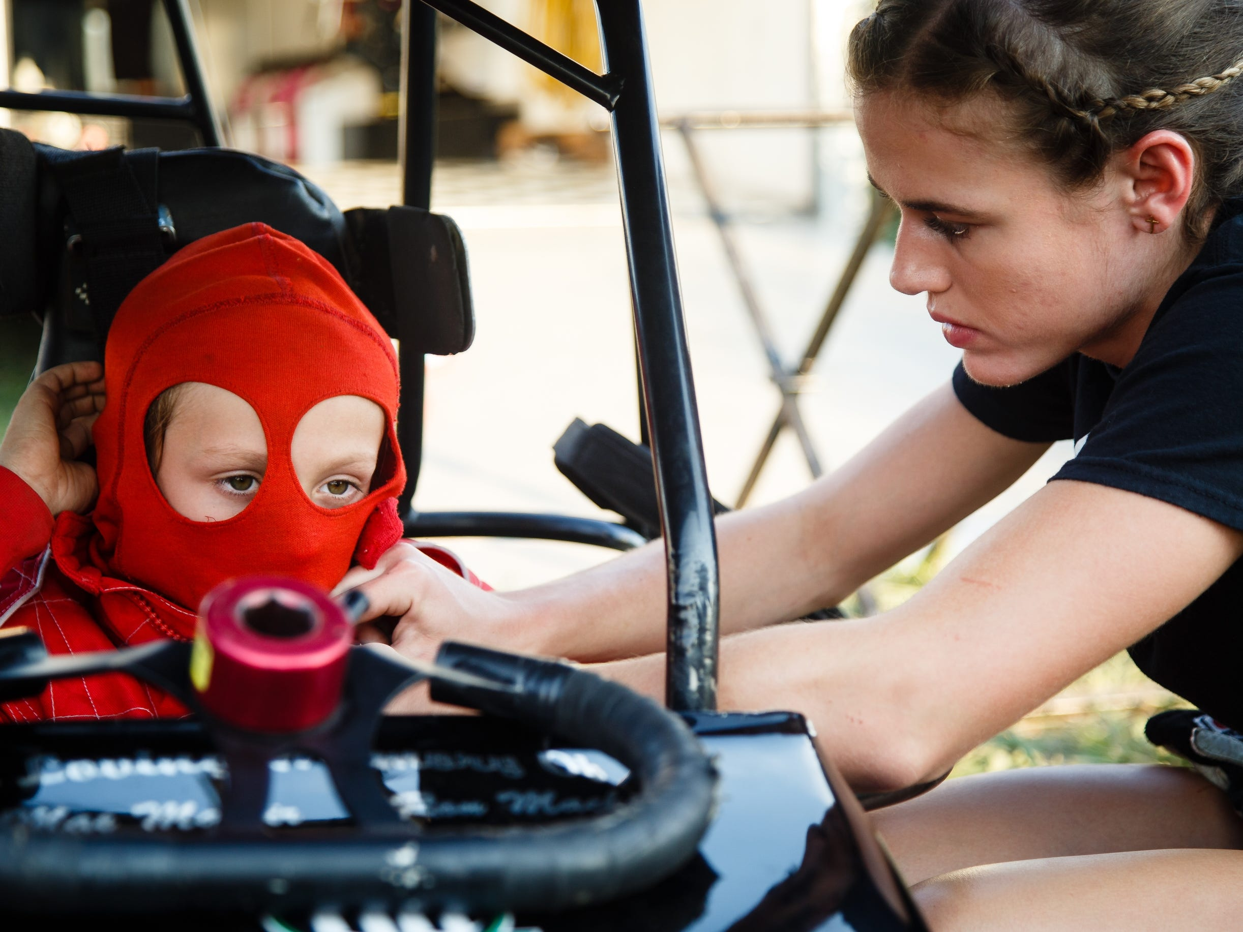 McKenna Haase helps Garrett Tatnell, 7 of Minneapolis, put on his racing gear during Nationals at the English Creek Speedway on Tuesday, Aug. 7, 2018 in Knoxville. Tatnell races with Haase's development team, Compass Racing, that she started when she was 17.