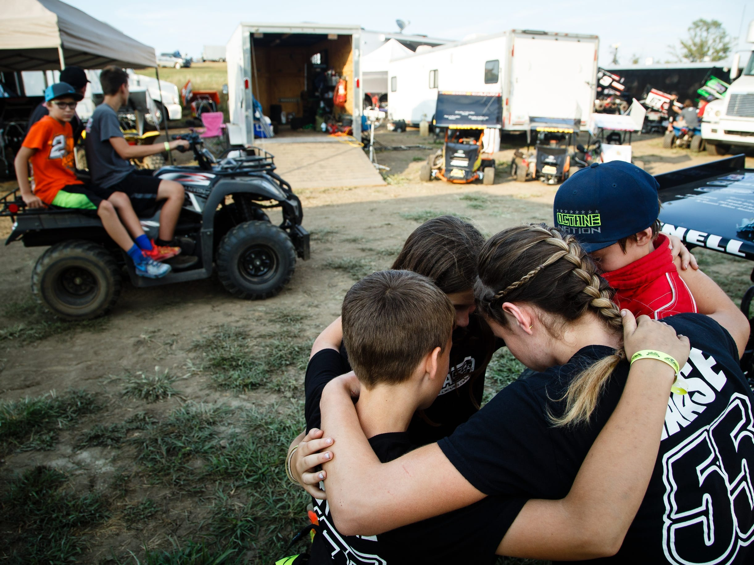 McKenna Haase, bottom right, leads her racing development team in saying the Racer's Prayer before they race during Nationals at the English Creek Speedway on Tuesday, Aug. 7, 2018 in Knoxville.