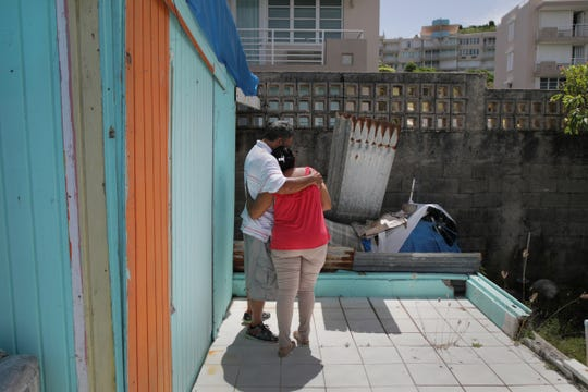 Luz Delgado comforts her husband Eleobadis Delgado after he got emotional while talking about the hardships he and fellow Puerto Ricans are experiencing physically and emotionally since Hurricane Maria devastated the island ten months prior in Maunabo, Puerto Rico on Wednesday, July 25, 2018.