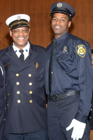 Detroit fire chief Jack Wiley with his son, firefighter Jack Wiley II, pose for a photo during graduation in downtown Detroit on November 3, 2015.