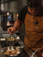 Gratiot Avenue Provisions Chef Aramis Jones prepares seared scallops during a pop-up dinner previewing the new charcuterie brand's forthcoming restaurant.