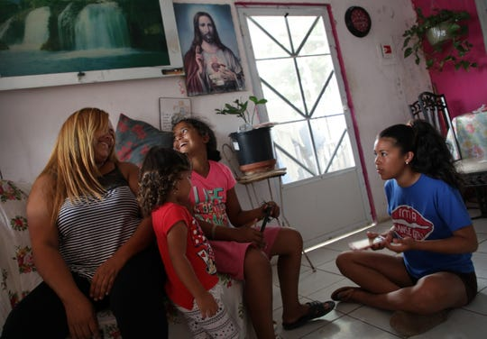 Liz Velazquez, from left, shares a laugh with Tayra Beltan, 2 and Nayeli Aponte, 12 as Neysha Gonzalez, 13, looks on in the living room they share with 5 other family members in Yabucoa, Puerto Rico on Wednesday, July 25, 2018. Several members of the family had to move in together after their homes were damaged by hurricane Maria and the now nine family members share the first floor of a house not yet fixed.