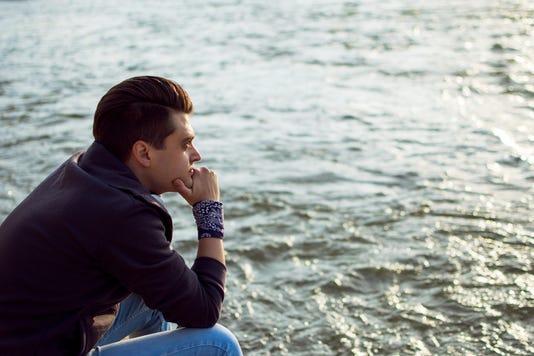 Sad Man Sitting Near The City River