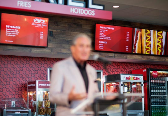 Proposed concession stand menu prices are displayed as Atlanta Falcons owner Arthur Blank speaks during a news conference inside the Falcons new stadium currently under construction Monday, May 16, 2016, in Atlanta. Falcons owner Arthur Blank says the Mercedes-Benz Stadium is on schedule to open in June, 2017 as scheduled and he's hoping it will be announced next week as the site of a Super Bowl. The Falcons also unveiled their new food and beverage plan which includes $2 hot dogs and soft drinks, a sharp decrease from current prices at the Georgia Dome. (AP Photo/David Goldman)