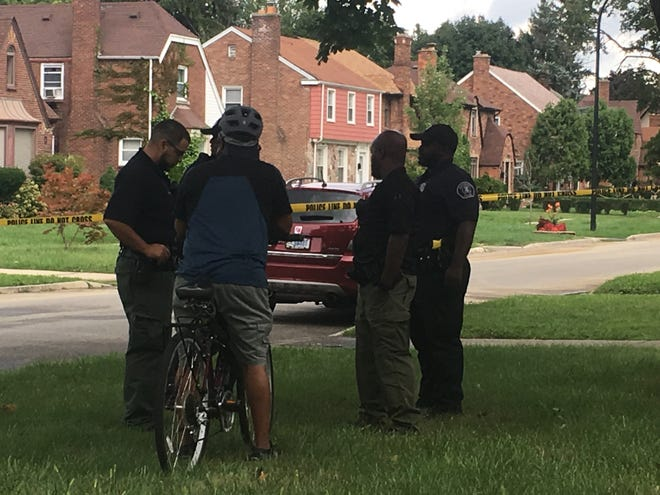 Detroit police officers interview a resident on Penrod, where city firefighter Jack Wiley Jr. was found shot to death in his home on Tuesday, Aug. 21, 2018.