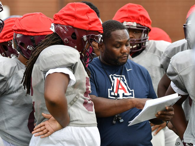 Harper Woods coach Rod Oden shows a play to the linemen during practice on Tuesday.