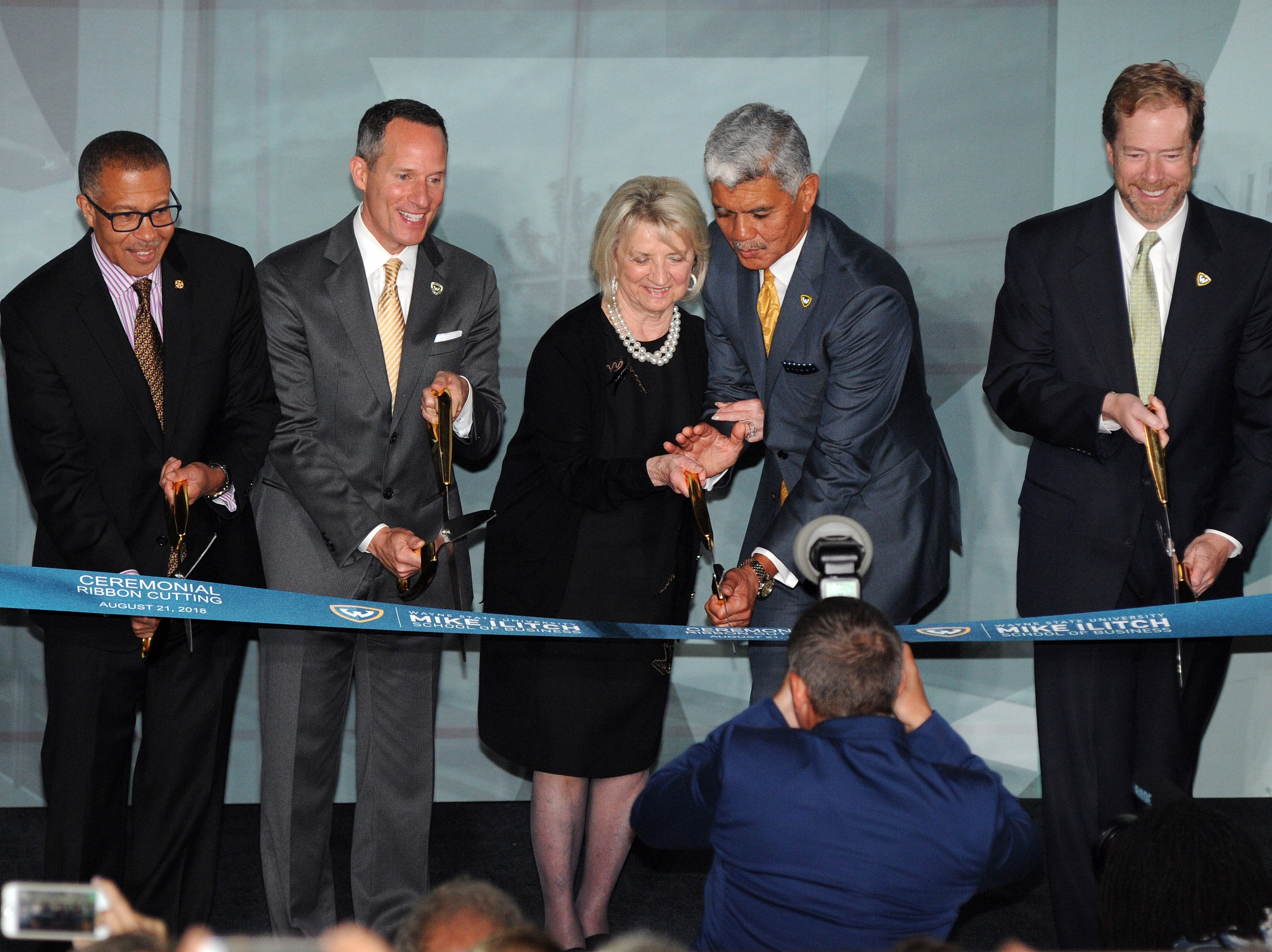 From left, Detroit Police Chief James Craig, Ilitch Holdings President and CEO Christopher Ilitch, Marian Ilitch, WSU President M. Roy Wilson, and WSU Board of Governors Vice Chair David Nicholson were some of the dignitaries involved in the ribbon-cutting ceremony for the new Mike Ilitch School of Business, Tuesday.
