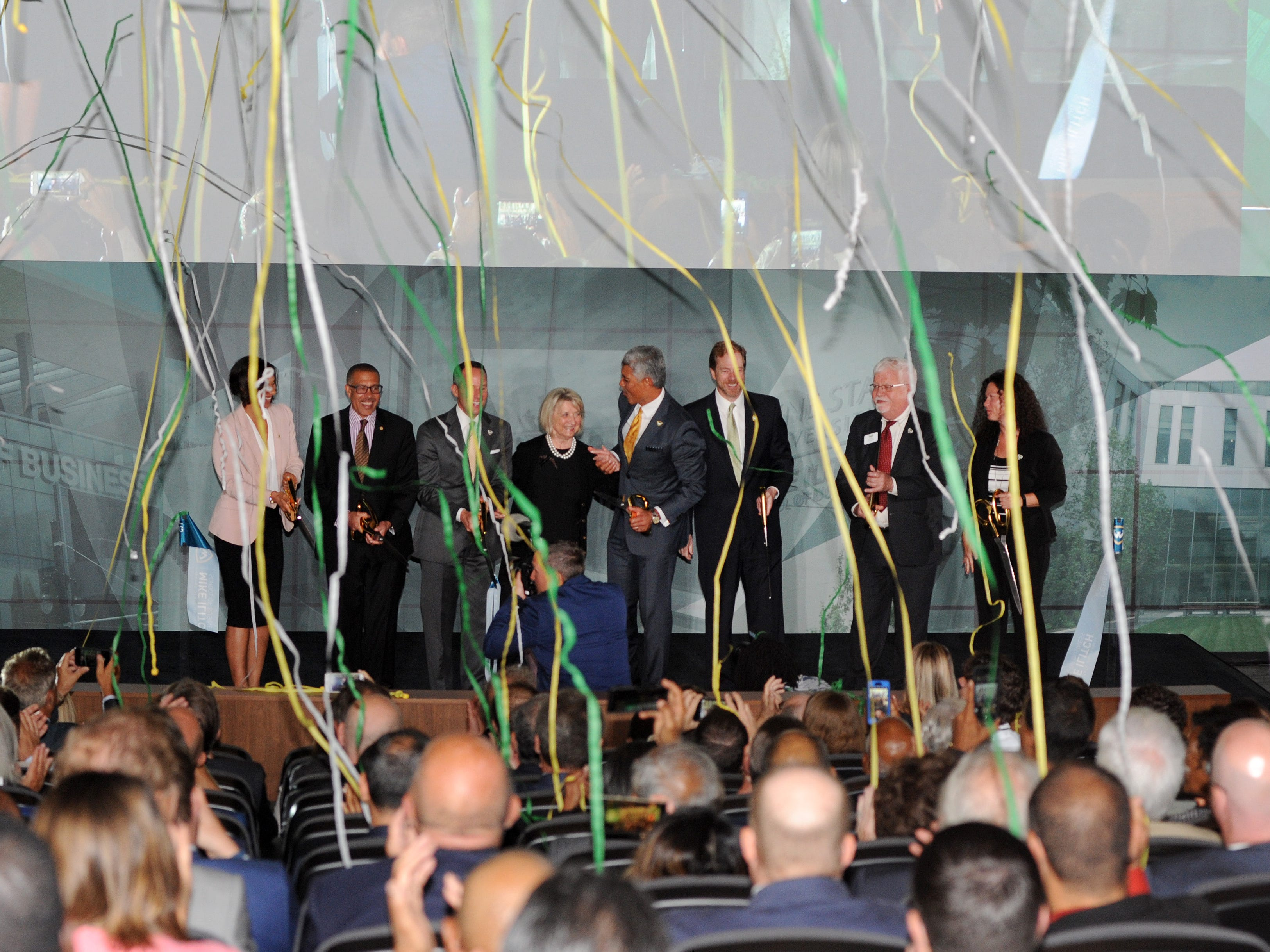 Following the ribbon cutting ceremony for the new Mike Ilitch School of Business, confetti streams rain down onto attendees from the ceiling.
