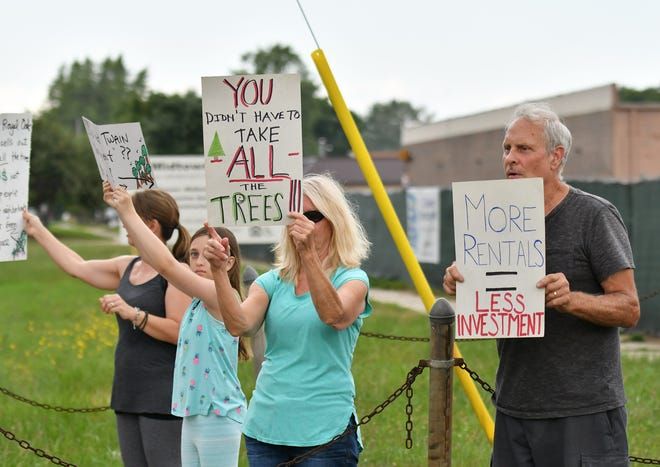 Jack Wall of Royal Oak, right, stands with other residents protesting in front of a construction site on Campbell Road just south of W. Fourteen Mile Road in Royal Oak on Aug. 8.